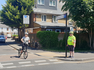 Image of a cyclist and a trainer on a Hounslow road.