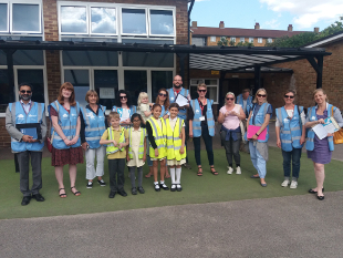 A group photo of council officers, councillors, teachers and school children.