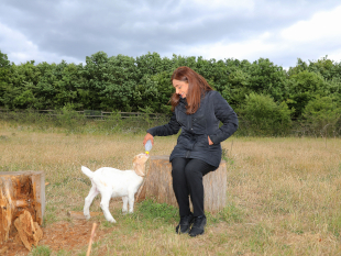 Image of Cllr Samia Chaudhary feeding one of the new born goat kids.