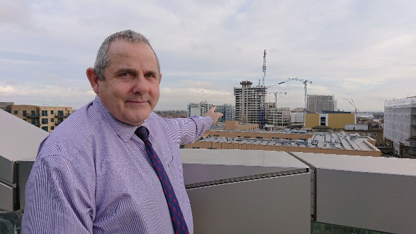 Image of Cllr Curran at Hounslow House pointing to the High Street Quarter development.
