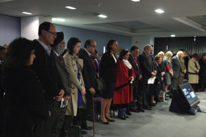 Image of invited guests holding a minute silence.