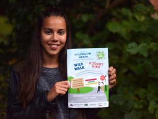 Image of a girl holding up the Hounslow Heath Nature walks poster