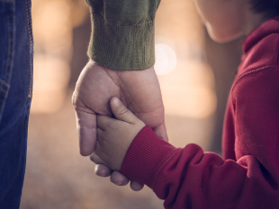 Image of a father and son holding hands.