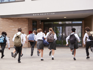 Image of secondary school children running to class