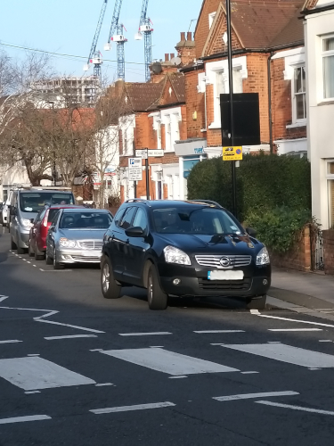 Image of a car parked on white zig-zag lines.