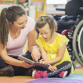 Child with special educational needs being shown a book