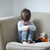 Child sits alone on sofa with teddy bear