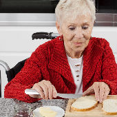 woman in wheelchair buttering toast