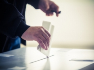 Image of a person submitting their ballot card.