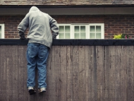 Image of a boy jumping over a fence in a residential area.