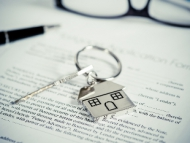 Image of a house key on a paper contract