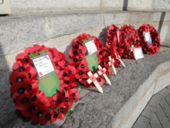 Wreaths lay next to Hounslow War Memorial, Hounslow High Street
