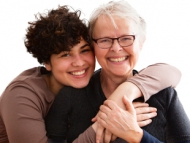 Image of senior woman and caregiver embrace