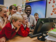 Children in a classroom with class teacher laughing
