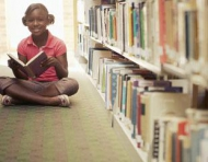 Young girl reading at the library