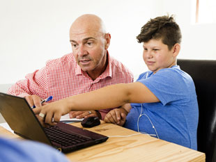 Father and son reading information on a laptop