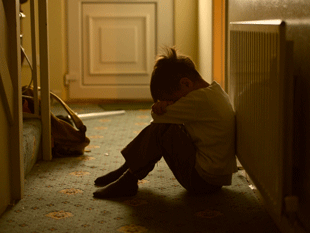 Image of a young boy sitting in the corridor alone